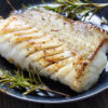 Close Up Of A Cod Fillet With Rosemary On A Plate